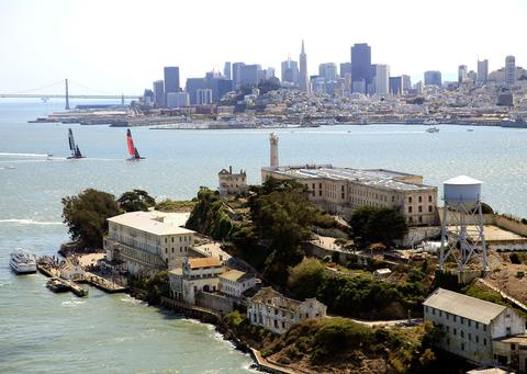 Emirates Team Zew Zealand races ahead of Oracle Team USA as they pass in front of Alcatraz Island and the San Francisco skyline during race 5 of the America's Cup Finals on September 10, 2013 in San Francisco, California.