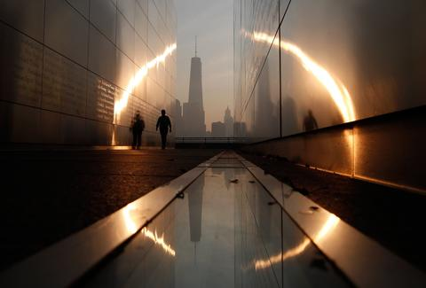 A man walks through the 9/11 Empty Sky memorial at sunrise across from New York's Lower Manhattan and One World Trade Center in Liberty State Park in Jersey City, New Jersey, September 11, 2013. Americans will commemorate the 12th anniversary of the September 11 attacks with solemn ceremonies and pledges to not forget the nearly 3,000 killed when hijacked jetliners crashed into the World Trade Center, the Pentagon, and a Pennsylvania field.