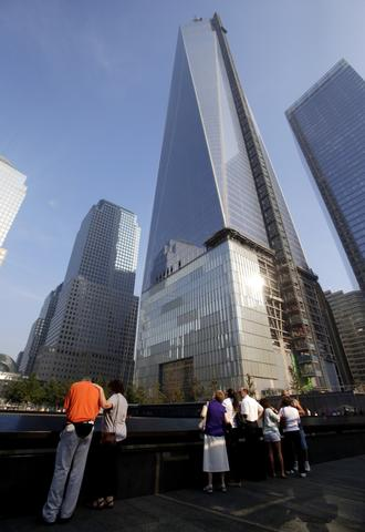 Mourners stand near One World Trade Center at the 9/11 Memorial during ceremonies marking the 12th anniversary of the 9/11 attacks on the World Trade Center in New York, on September 11, 2013.