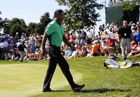 Tiger Woods walks off the 13th hole on the first round of the BMW Championship at Conway Farms Golf Club in Lake Forest on Thursday.