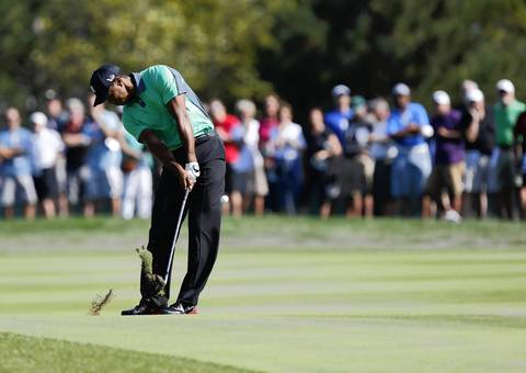 Tiger Woods hits his ball on the 10th fairway on the first round of the BMW Championship at Conway Farms Golf Club in Lake Forest on Thursday.