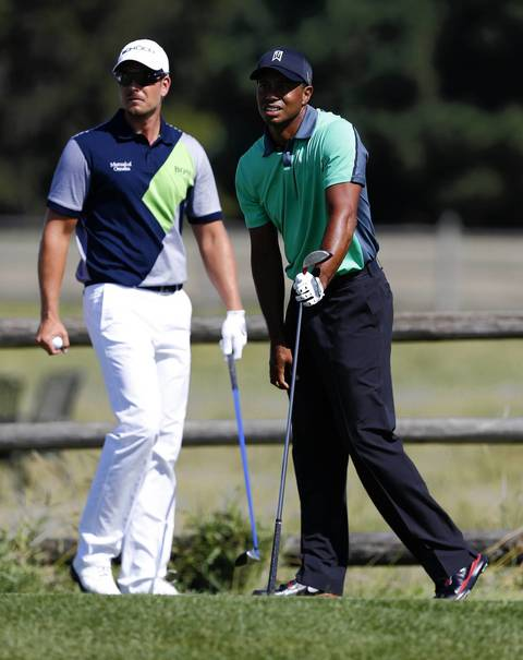 Tiger Woods watches the flight of his ball after teeing off the 12th as Henrik Stenson looks on at the first round of the BMW Championship at Conway Farms Golf Club in Lake Forest on Thursday.