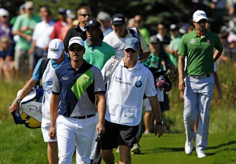 Henrik Stenson, Tiger Woods and Adam Scott approach the 11th hole on the first round of the BMW Championship at Conway Farms Golf Club in Lake Forest on Thursday.