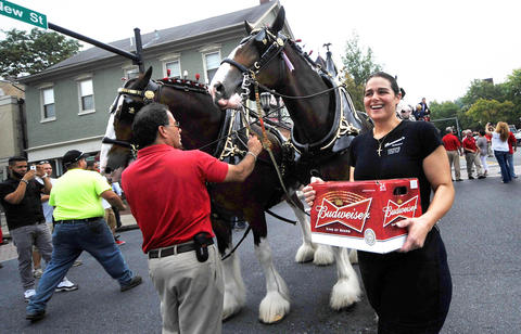 The Budweiser Clydesdales makes their way north on New Street Thursday afternoon. Rosanna Crisci, owner of Rosanna's Restaurant at New and Broad Streets, receives a case of beer from the Clydedales' delivery.