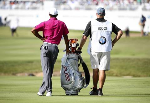 Tiger Woods and his caddie wait to approach the 18th hole.