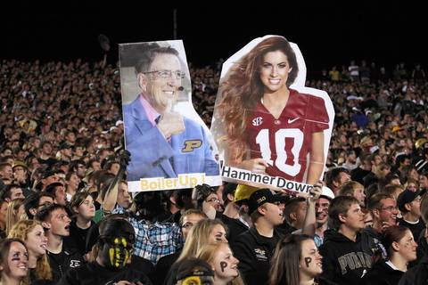 Purdue fans hold up signs of A.J. McCarron's girlfriend Katherine Webb and ABC announcer Brent Musberger.