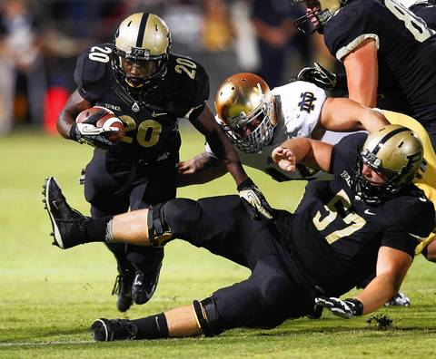 Purdue's Dalyn Dawkins runs the ball as Carlo Calabrese converges for the tackle and Robert Kugler trips him up.