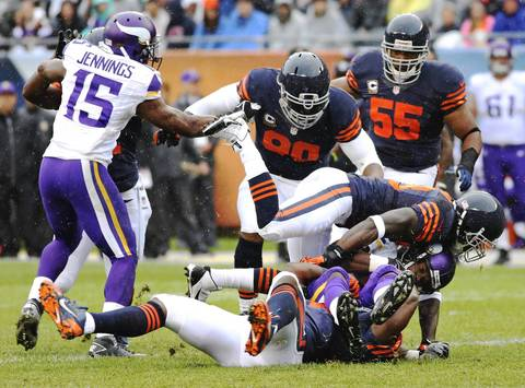 Adrian Peterson of the Vikings is tackled by the Bears defense in the first quarter at Soldier Field.