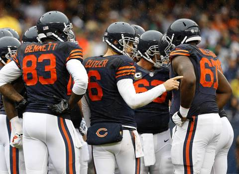 Chicago Bears quarterback Jay Cutler (6) talks with Chicago Bears offensive tackle Jordan Mills (67) during a pause against the Minnesota Vikings in the first quarter.