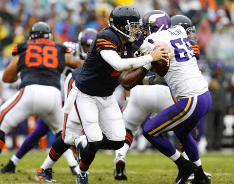 Chicago Bears quarterback Jay Cutler (6) runs away from Minnesota Vikings defensive end Jared Allen (69) and is able to make a complete pass in the first quarter at Soldier Field.