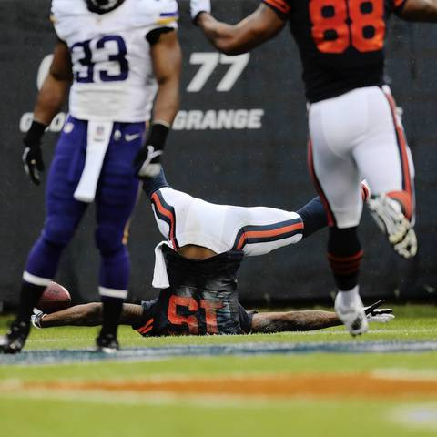 Chicago Bears' wide receiver Brandon Marshall (15) tumbles after catching a pass by quarterback Jay Cutler (6) for a touchdown during the first half.
