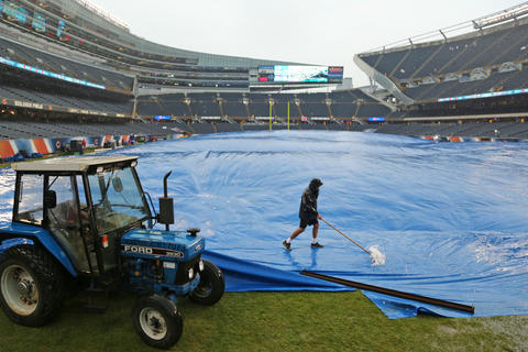 The grounds crew pushes off rain water on a tarp covering the grass prior to an NFL football game between the Chicago Bears and the Minnesota Vikings Sunday at Soldier Field in Chicago.