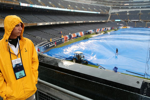Ushers watch as ground crews work on the turf prior to an NFL football game between the Chicago Bears and the Minnesota Vikings Sunday, Sept. 15, 2013 at Soldier Field in Chicago.