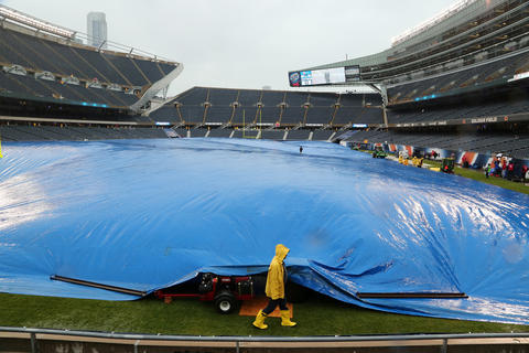 Ground crews work walk past a tarp covering the grass prior to an NFL football game between the Chicago Bears and the Minnesota Vikings Sunday at Soldier Field in Chicago.