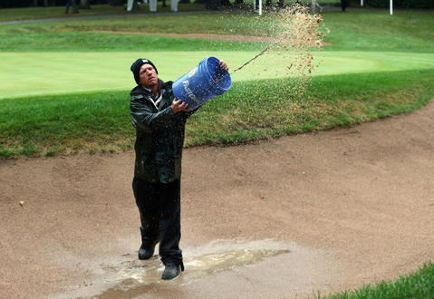 Volunteer Ben Pfeffer removes water from the bunker on the 1st hole during the rain delay on the last round of BMW Championship at Conway Farms Golf Club, in Lake Forest, Ill., on Sunday.