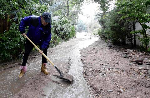 John McElveen shovels silt and debris out of the path of the rising water in Boulder, Colo.