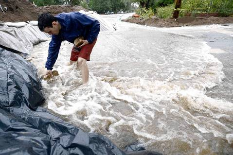 Erez Shani adds rocks to hold the plastic sheeting in place as heavy rains cause flooding to rise in Boulder, Colo.