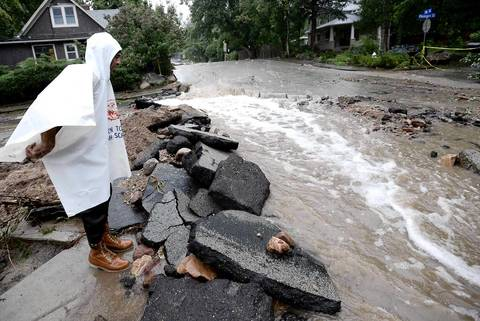 Resident John Hoffenberg watches the flow of water in Boulder, Colo.