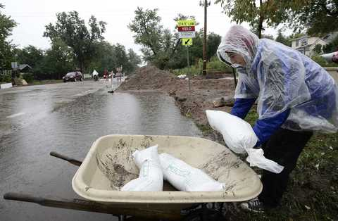 Aaron Hoffenberg loads a wheelbarrow with sand bags in Boulder, Colo.