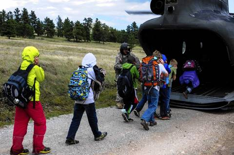 Children from Cal-Wood Education Center in Jamestown, Colo., board a rescue helicopter.