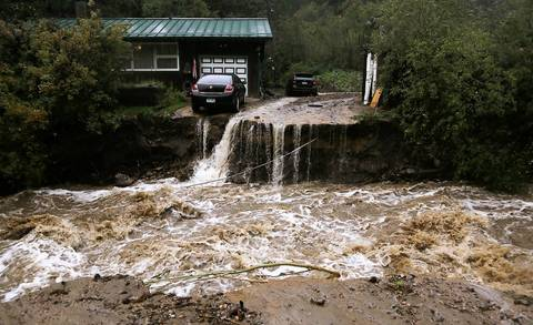 A home and car are stranded after a flash flood in Coal Creek destroyed the bridge near Golden, Colorado Sept. 12, 2013.