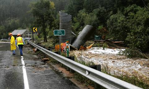 Culverts and a boat are piled up after a flash flood in Coal Creek destroyed bridges near Golden