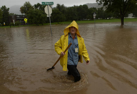 Shanda Brisdin tries to clear street drains in north Boulder, September 12, 2013.