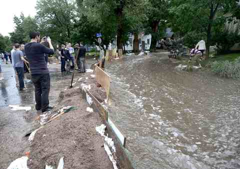 Neighbors survey a dike created to funnel water down 7th Street as heavy rains cause severe flooding in Boulder, Colorado, September 12, 2013.