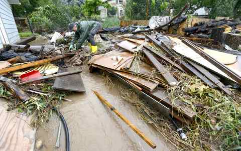 A man (requested his name not be used) tries to untangle debris that have been washed down to his home after severe flooding in Boulder, Colorado September 12, 2013.
