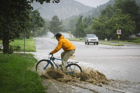 A mountain biker tests his skills taking on 6-10 inches of rain during flooding in Boulder Creek.