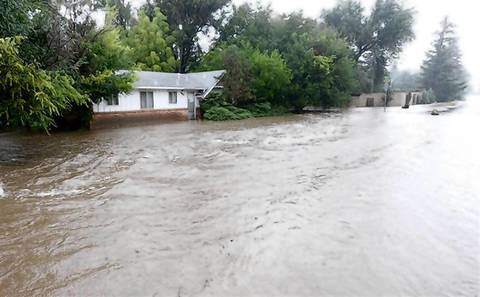 Water runs freely down Topaz Drive as heavy rains cause severe flooding in Boulder, Colo.