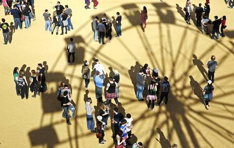The shadow of a ferris wheel is cast on the ground and on concert-goers.