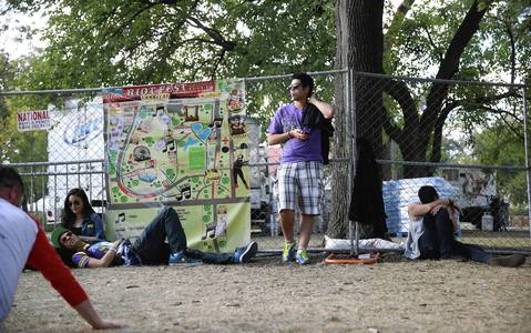 Concertgoers find spots along a fence.