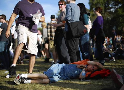 A concertgoer steps over Tom Henkel of Indianapolis, Ind., as he naps on the ground.
