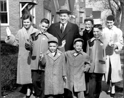 On the way to the polls, the family of Richard J. Daley keep fingers crossed and wear smiles as bright as the sunny day itself in 1955. (Left to right, front) Richard, 12, John, 8, Bill, 6, Mike, 11. (Left to right, rear) Eleanor, 14, Richard Daley, Mrs. Eleanor Daley, Mary Carol, 16.