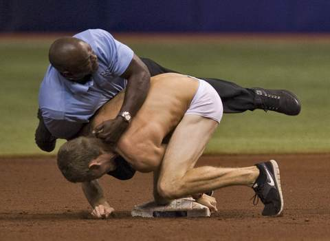 A security personnel (L) tackles a man who ran onto the field in his underwear as he tries to steal second base during the fifth inning of a MLB American League baseball game between the Texas Rangers and Tampa Bay Rays in St. Petersburg, Florida, September 16, 2013.