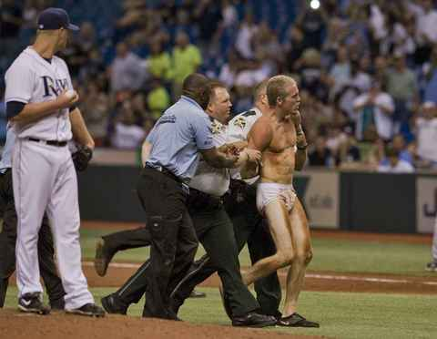 Tampa Bay Rays starter Alex Cobb (L) looks on from the mound as security personnel arrest a fan who leaped onto the field wearing only his underwear during the fifth inning of their MLB American League baseball game against the Texas Rangers in St. Petersburg, Florida, September 16, 2013.