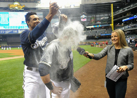 Sep 16, 2013; Milwaukee, WI, USA; Milwaukee Brewers left fielder Caleb Gindl (center) is doused with powder by center fielder Carlos Gomez (left) during an interview with reporter Sophia Minnaert after the Brewers beat the Chicago Cubs 6-1 at Miller Park. Gindl had 3 hits, scored 3 runs and had 3 RBIs.
