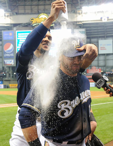 Sep 16, 2013; Milwaukee, WI, USA; Milwaukee Brewers left fielder Caleb Gindl is doused with powder by center fielder Carlos Gomez after the Brewers beat the Chicago Cubs 6-1 at Miller Park. Gindl had 3 hits, scored 3 runs and had 3 RBIs.