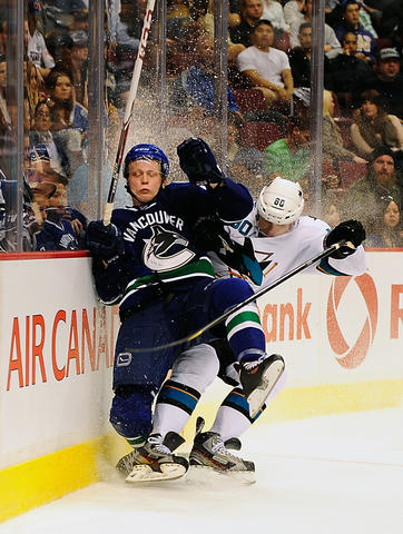Sep 16, 2013; Vancouver, British Columbia, CAN; Vancouver Canucks defenseman Andrew Alberts (41) is boarded by San Jose Sharks defenseman Matt Tennyson (80) during the third period at Rogers Arena. The San Jose Sharks won 3-2.