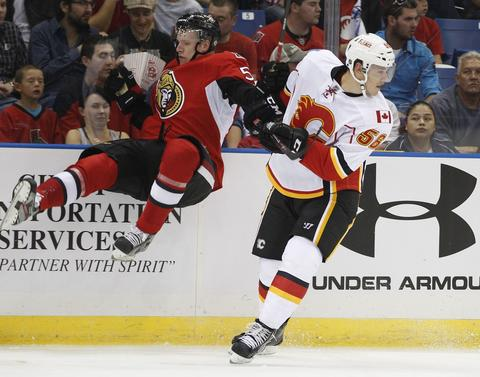 Calgary Flames defenceman Tyler Wotherspoon (R) roughs up a flying Ottawa Senators Cody Ceci during the second period of their NHL hockey game in Saskatoon, Saskatchewan September 16, 2013.