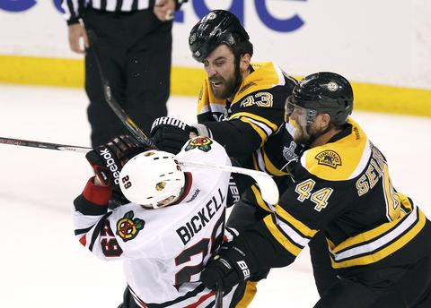 Boston Bruins' Zdeno Chara (33) and Dennis Seidenberg hit Chicago Blackhawks' Bryan Bickell during the third period  in Game 3 of their NHL Stanley Cup Finals hockey series in Boston, Massachusetts, June 17, 2013.