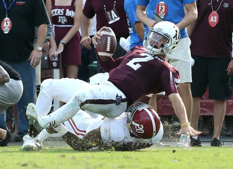 Sep 14, 2013; College Station, TX, USA; Texas A&M Aggies quarterback Johnny Manziel (2) is horse collar tackled by Alabama Crimson Tide safety Jarrick Williams (20) at Kyle Field. Alabama Crimson Tide beat the Texas A&M Aggies 49-42.