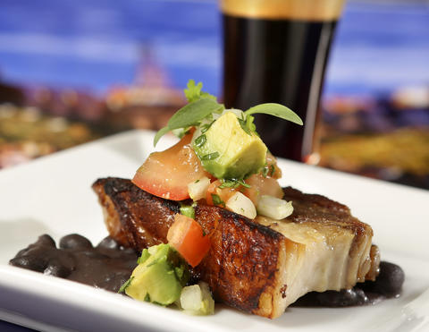 The Crispy Pork Belly with Black Beans, Onions, Avocado and Cilantro, with Cerveharias Kaiser Brewery Xingu Black Beer (background), from the new Brazil kiosk, featured in the upcoming 2013 edition of the Epcot International Food & Wine Festival, which runs Sept. 27 through November 11. Photographed Friday, August 23, 2013, in an exclusive Orlando Sentinel behind-the-scenes preview. (Joe Burbank/Orlando Sentinel) B583075881Z.1