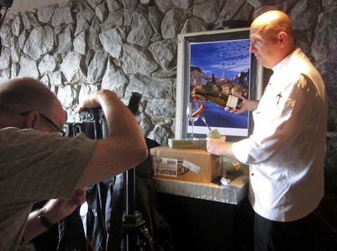 Behind The Scenes -- From Prototype to Production, the 2013 Epcot Food & Wine Photo-shoot: Step 5: August 23, the exclusive preview shoot for the Orlando Sentinel, which I used studio strobes to light the dishes in front of the poster print of France at Sunset. In this photo, Chef Jens Dalhmann, Executive Chef for Epcot and the Epcot International Food & Wine Festival, prepares to pour wine during the cover shoot in front of the poster print.  (Joe Burbank/Orlando Sentinel)..