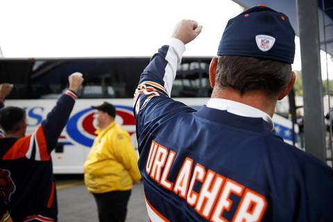Bears fan Dan King of Danville, Kentucky (right) cheers as Bears team bus arrives.