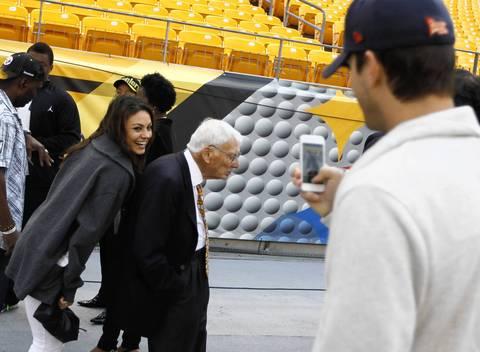 Actress Mila Kunis sneaks next to Steelers owner Dan Rooney while boyfriend Ashton Kutcher takes a picture.