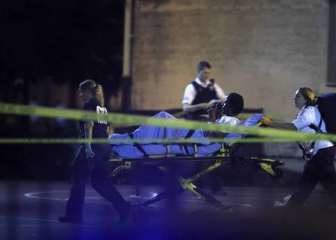 Emergency personnel transport victims from the scene where 13 people, including a 3-year-old, were shot at Cornell Square Park in the Back of the Yards neighborhood.