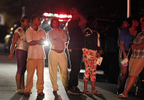 People gather in the 5100 block of South Wood Stret after multiple shooting victims are attended to and moved to waiting ambulances near Cornell Square Park in the Back of the Yards neighborhood Thursday night.