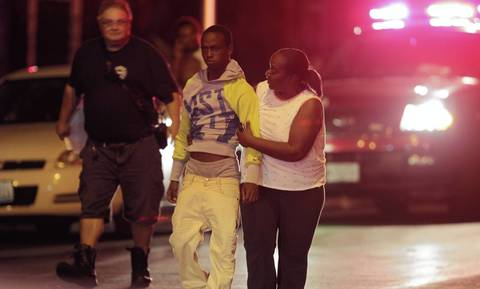 A person is escorted away from a scuffle that occurred following a multiple shooting near the intersection of 50th and Wood Streets in Chicago. At least 13 people were shot, including a 3-year-old, in the incident.